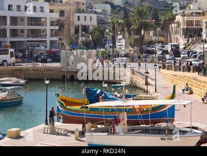 Spinola Bay in St. Julian's Malta eine geschützte Bucht mit Fischerbooten, Verkehr, Restaurants und Unterkünfte für Touristen, Blick der Liebe Brücke Stockbild
