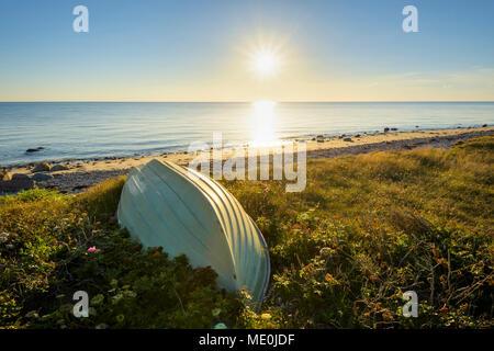 Kleines Boot auf dem Kopf am Strand bei Sonnenuntergang im Sommer bei Sealand Odde in Odsherred an der Ostsee in Seeland, Dänemark Stockbild