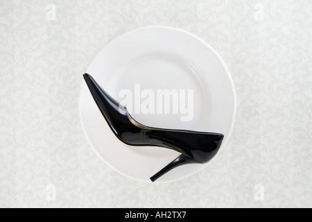 schwarze high Heel auf weißen Teller, Studio gedreht Stockbild
