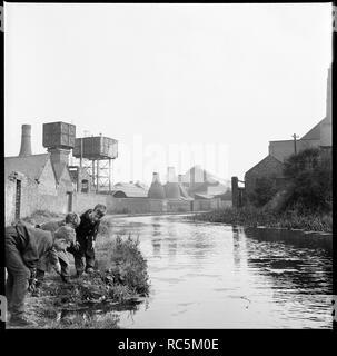 Caldon Canal, Joiner's Square, Hanley, Stoke-on-Trent, Staffordshire, 1965-1968. Drei Jungen, die Kontrolle der Gewässer der Caldon Canal, die von einem Punkt auf dem Leinpfad neben Trent Arbeiten, mit den Öfen der Tischler Square Mühle im Hintergrund. Stockbild