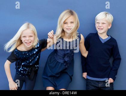 Porträt der Geschwister vor blauem Hintergrund Stockbild