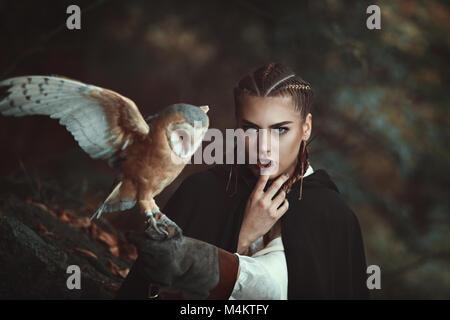 Frau mit schleiereule auf ihren Arm. Wald Hintergrund Stockbild