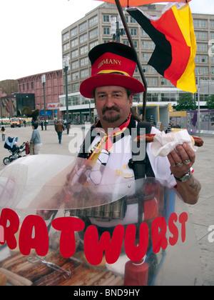 Mann, Verkauf von traditionellen Bratwurst Wurst Hotdogs aus mobilen Stall in Berlin Deutschland Stockbild
