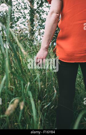 Frau zu Fuß durch ein Feld lange Gras Stockbild