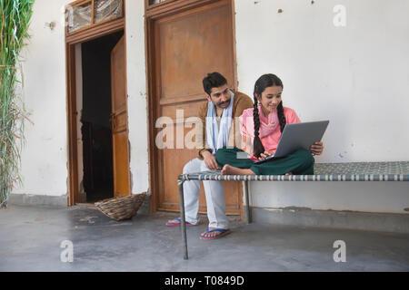 Happy Village Mädchen sitzen mit ihrem Vater auf einem Feldbett, die ein Laptop. Stockbild