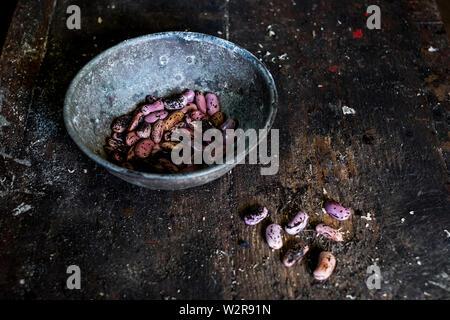 Hohen Winkel in der Nähe von grau Metallschale mit Lila gesprenkelten Bohnen auf Holztisch. Stockbild