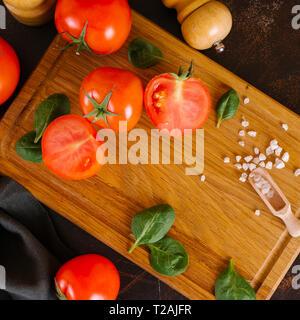 Frische Tomaten mit Basilikum auf Holzbrett Stockbild