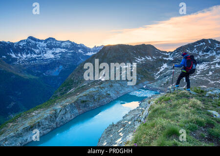 Ein Wanderer sieht auf See Pirola von oben bei Sonnenaufgang, Chiareggio Tal, Valmalenco, Valtellina, Lombardei, Italien, Europa Stockbild