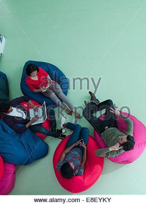 Männer und Frauen, die mit Laptop und Handy in den Sitzsäcken Stockbild