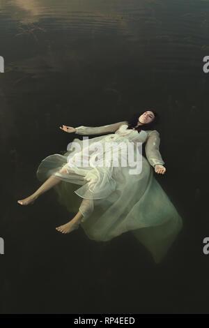 Frau floating im grünen See Gewässer Stockbild