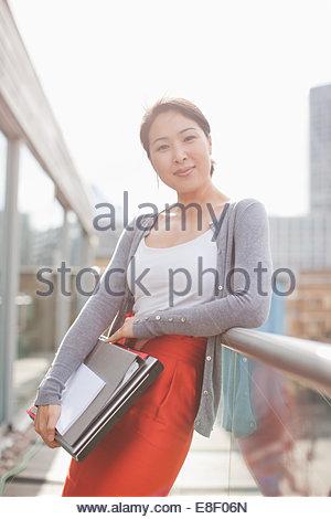 Lächelnde Geschäftsfrau hält Ordner und stützte sich am Geländer des städtischen Balkon Stockbild