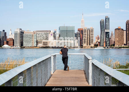Besucher auf eine Brücke über die Sumpfgebiete, mit Blick auf den East River und Midtown Manhattan. Hunters Point South Park, New York, United States. Architekt: Stockbild