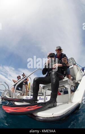 Crew hilft Tauchern mit Sicherheit prüfen Sie vor dem Eindringen von Wasser Stockbild