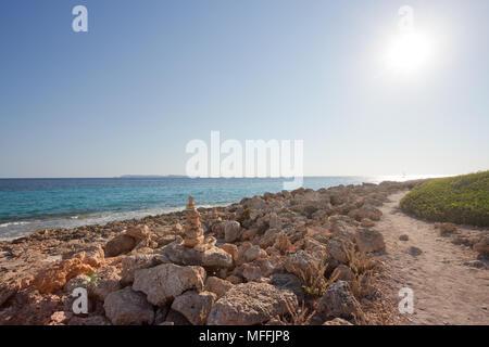 Cap de Ses Salines, Mallorca, Spanien - ein Spaziergang bei Sonnenuntergang in den felsigen Strand von Ses Salines Stockbild