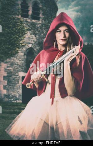 Frau trägt einen roten Umhang mit einem kleinen Schwert Stockbild