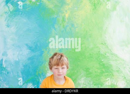 Kleiner Junge sitzt vor Grün und blau Malerei Stockbild
