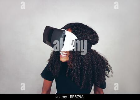 Eine schöne, junge schwarze Frau mit lockiges Afro-Haar seidig trägt Virtual Reality VR-Headset und spielt Videospiele, während im Studio lächelnd mit grauer Hintergrund Stockbild