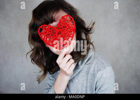 Junge Frau mit einem roten Herzen Stockbild