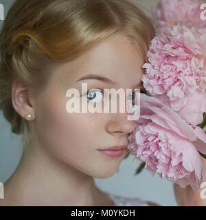 Nahaufnahme der Kaukasischen junges Mädchen mit Blumen zu Gesicht Stockbild