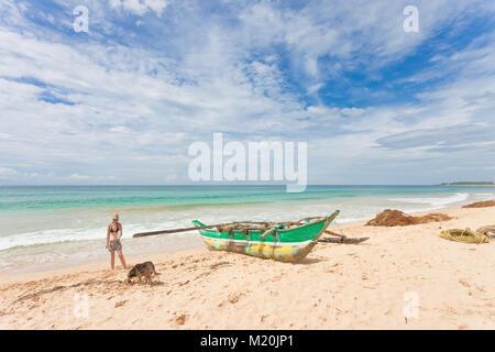 Balapitiya, Sri Lanka, Asien - eine Frau und ein Hund aus einem Spaziergang am Strand von Balapitiya Stockbild