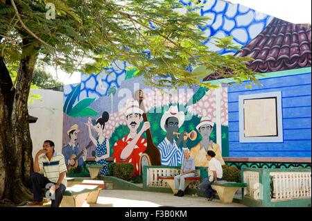 Männer sitzen plaudernd vor einem Wandbild von Musikern; Park in Baracoa, Provinz Guantánamo, Kuba Stockbild