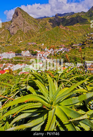 Spanien, Kanarische Inseln, Teneriffa, Taganana, Stadtbild mit Anagagebirge im Hintergrund und Aloe Pflanze im Vordergrund. Stockbild