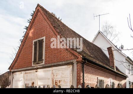 Alte, leere Backsteinhaus mit krummen Schornstein Stockbild