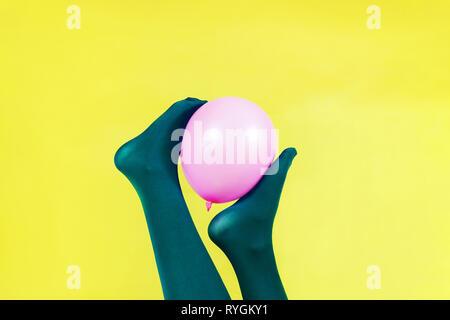 Grüne Beine von einer Frau mit einem Rosa Ballon gegen eine gelbe Wand Stockbild