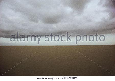Regenwolken über Strand, Niederlande Stockbild