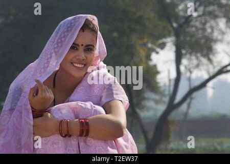 Nahaufnahme eines lächelnden ländliche Frau sitzt in der Nähe von Landwirtschaft Feld über dem Kopf mit Sari. Stockbild