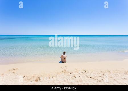 Lido Venere, Apulien, Italien - Eine junge Mutter sitzen am Strand mit Blick auf den Horizont Stockbild