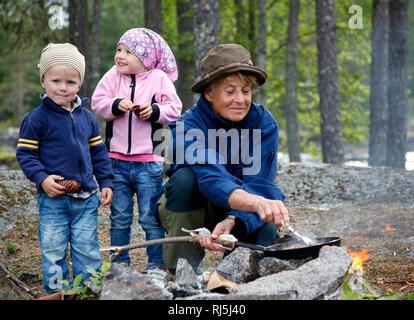 Familie kochen über Feuer Stockbild