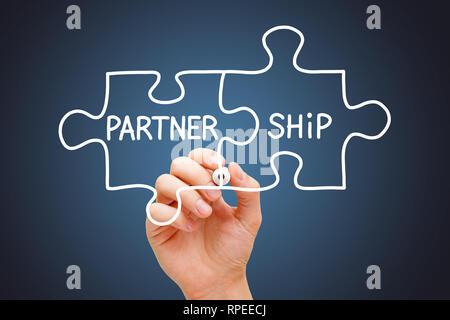 Handzeichnung Partnerschaft puzzle Business Konzept mit weißen Marker auf Transparenten abwischen Board auf dunkelblauem Hintergrund. Stockbild
