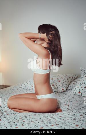 Schöne junge Frau auf einem weißen Bett Stockbild