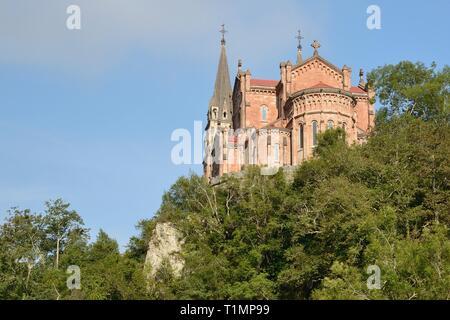 Basilica de Santa Maria La Real, von rosa Kalkstein gebaut, auf einem Baum bedeckte Hügel, Covadonga, Picos de Europa, Asturien, Spanien, August. Stockbild