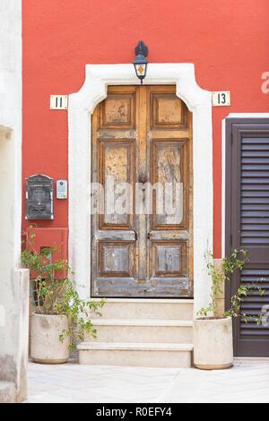 Presicce, Apulien, Italien - Eine alte hölzerne Tür und ein Bordeaux Fassade Stockbild