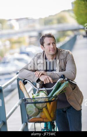 Porträt des Mannes hält Fahrrad mit Gemüse im Korb Stockbild