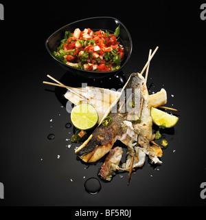Gegrillten Fisch-Spieße mit Kalk, grünem Chili und Salat, auf einem schwarzen Hintergrund Stockbild