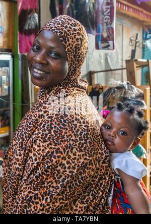 Afrikanische Mutter ihr Kind Mädchen tragen in ihren Rücken, Comoé, Abengourou, Elfenbeinküste Stockbild