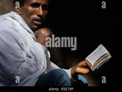 Orthodoxe Menschen beten mit Bibel, Amhara-region, Lalibela, Äthiopien Stockbild