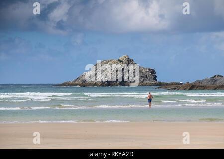Einen Urlauber, der im Meer bei Crantock Beach Blick auf die Gans unbewohnte Insel aus Osten Pentire Headland in Newquay in Cornwall. Stockbild