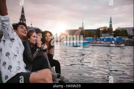 Schuss Gruppe von Menschen im Freien am Steg sitzen und Spaß haben. Freunde auf Pier über See in der Stadt Stockbild