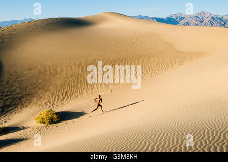 Nackte Frau in der Wüste laufen bis Düne Stockbild