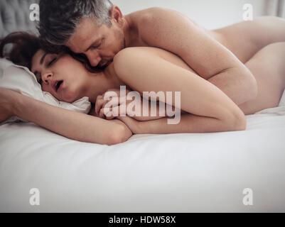 Leidenschaftliche Paare im Bett beim Sex. Junger Mann und Frau machen Liebe im Schlafzimmer. Stockbild