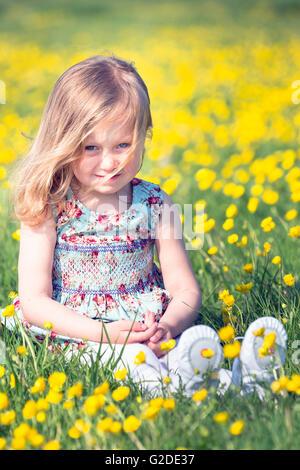 ein 3-jähriges Mädchen sitzt auf einer Blumenwiese Stockbild