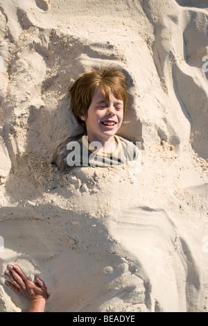 Ein kleiner Junge vergraben im Sand, Cable Beach, Nassau, Bahamas, Caribbean Stockbild