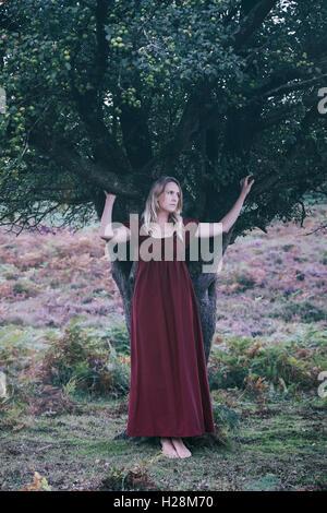 eine blonde Frau mit einem roten Kleid steht unter einem Baum Stockbild