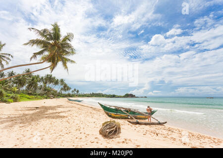 Balapitiya, Sri Lanka, Asien - eine Frau, die Vorbereitung auf eine Kanu Tour am Strand von Balapitiya Stockbild