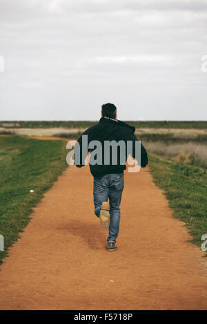 Mann mittleren Alters im ländlichen Küstenregion laufen Stockbild