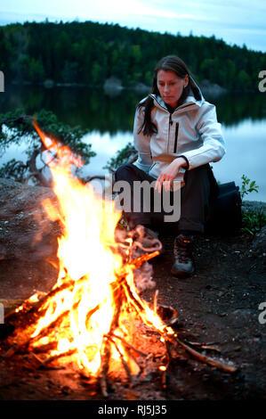 Frau sitzt bei einem Brand Stockbild